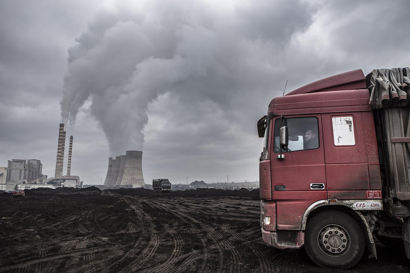 A truck driving by smokestacks. Air pollution in Greece is a mounting issue following the construction of new coal-fired energy plants.