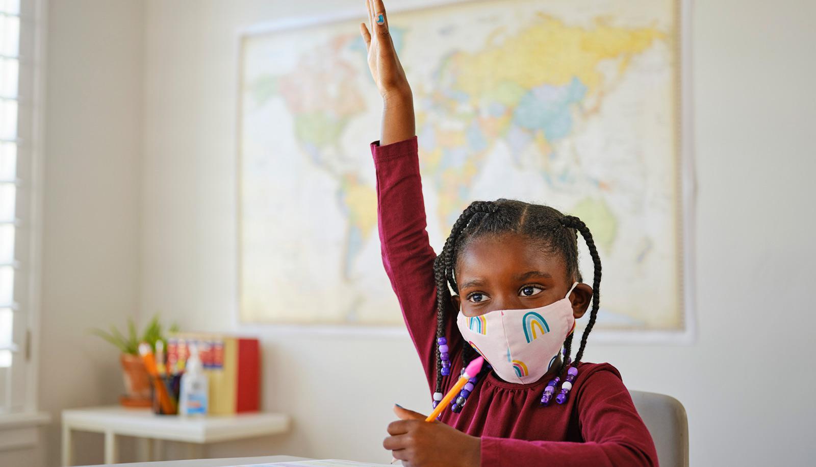 Black child in rainbow mask raises hand in classroom