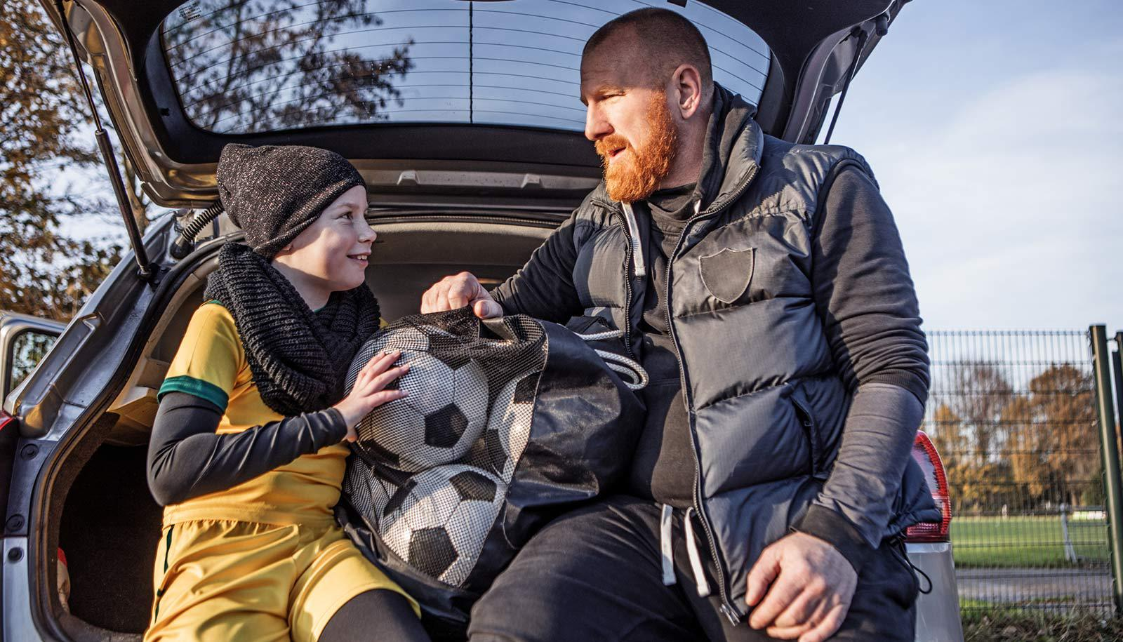 father and daughter sit in back of car with soccer balls