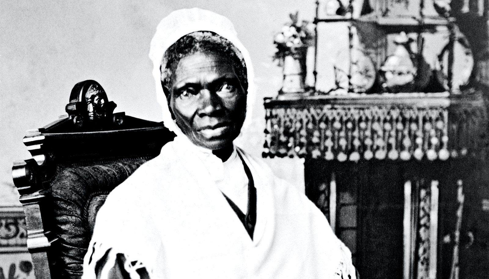Sojourner Truth sits in a chair looking at the camera, wrapped in a white shawl