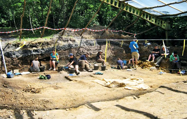 Researchers sit on the dirt at the dig site where they found the Rudapithecus fossil
