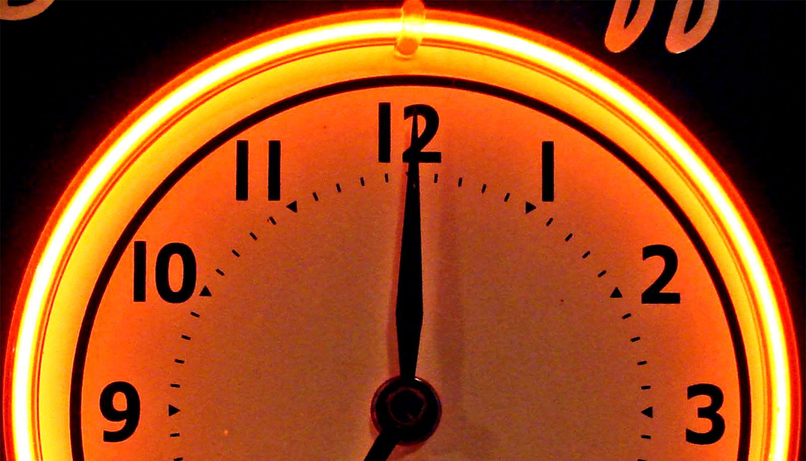 A clock glows red in neon light