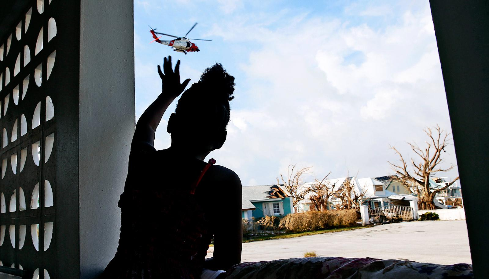 A young girl reaches up out of a window towards a rescue helicopter while in the background there are houses that have been damaged in the hurricane and a flooded street
