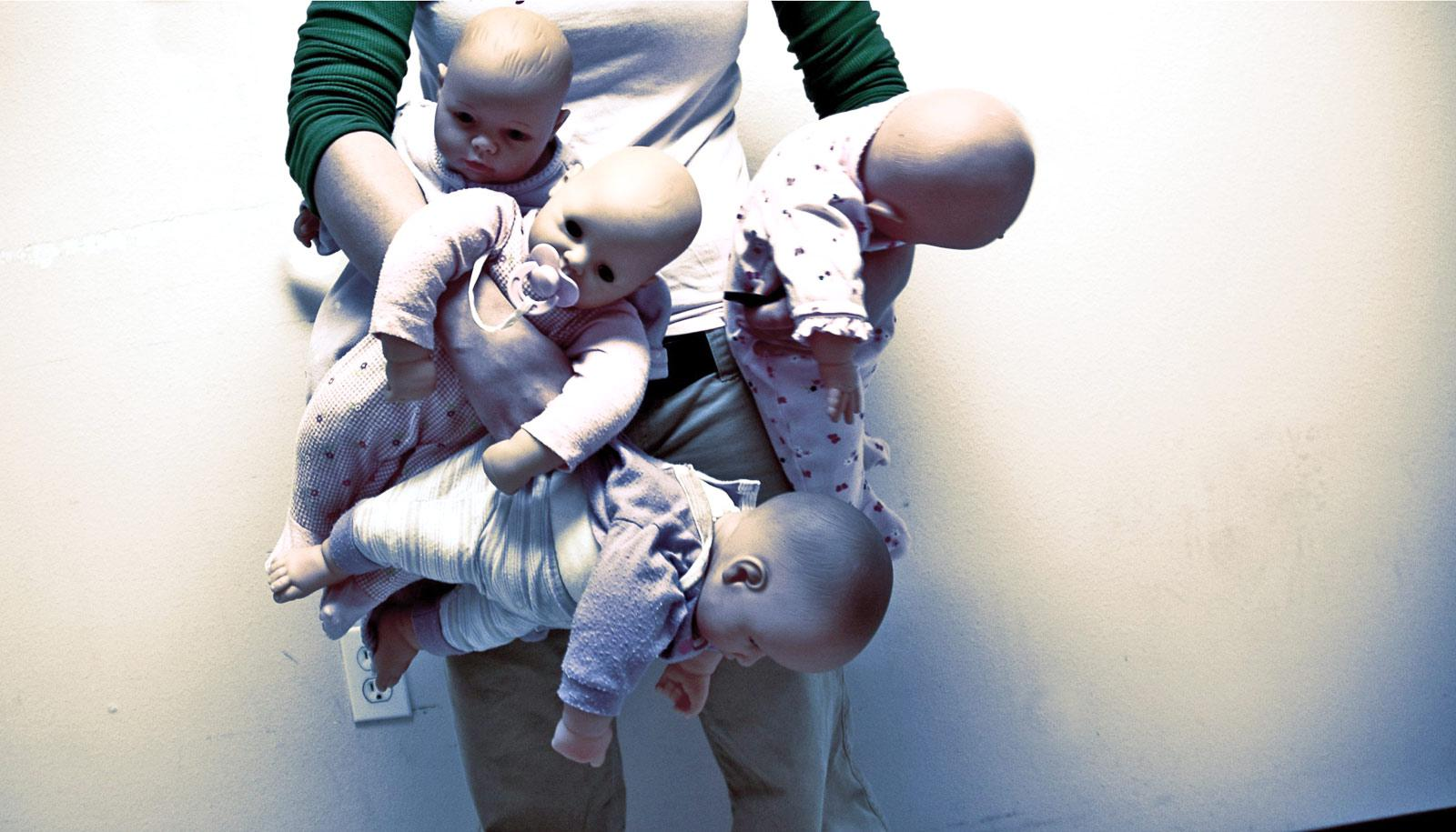 person holding four baby dolls