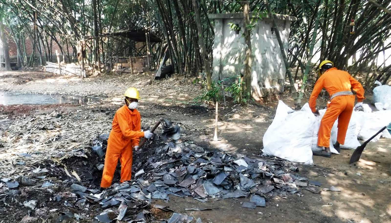 workers in orange suits in and near burn site