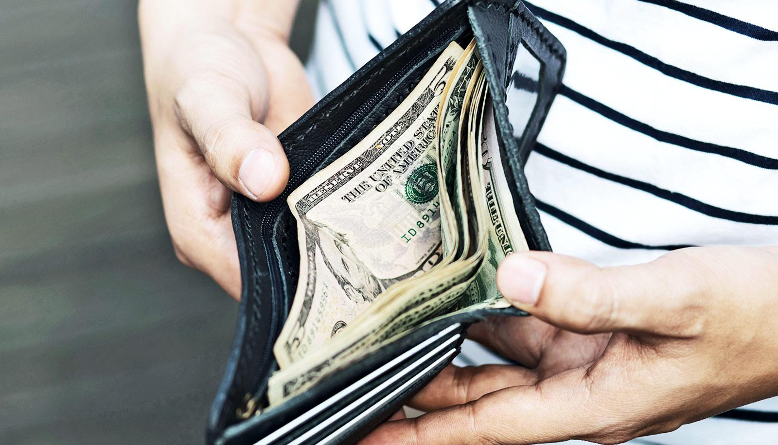 A man looks into his wallet at some cash