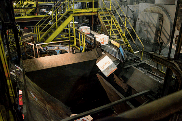 Boxes of unused medication tumble into the mouth of an incinerator at Curtis Bay Medical Waste Services in Baltimore, Maryland. (Matt Roth for ProPublica)