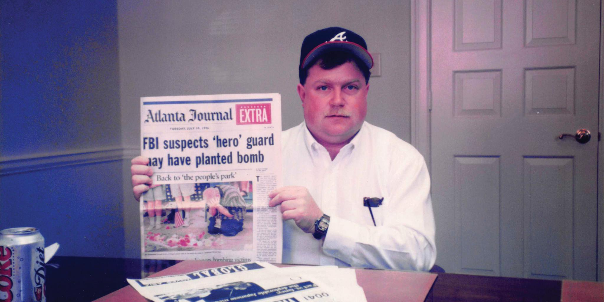 Hero No Longer Richard Jewell holds up the original Atlanta Journal-Constitution article that first identified him as the target of the FBI investigation.