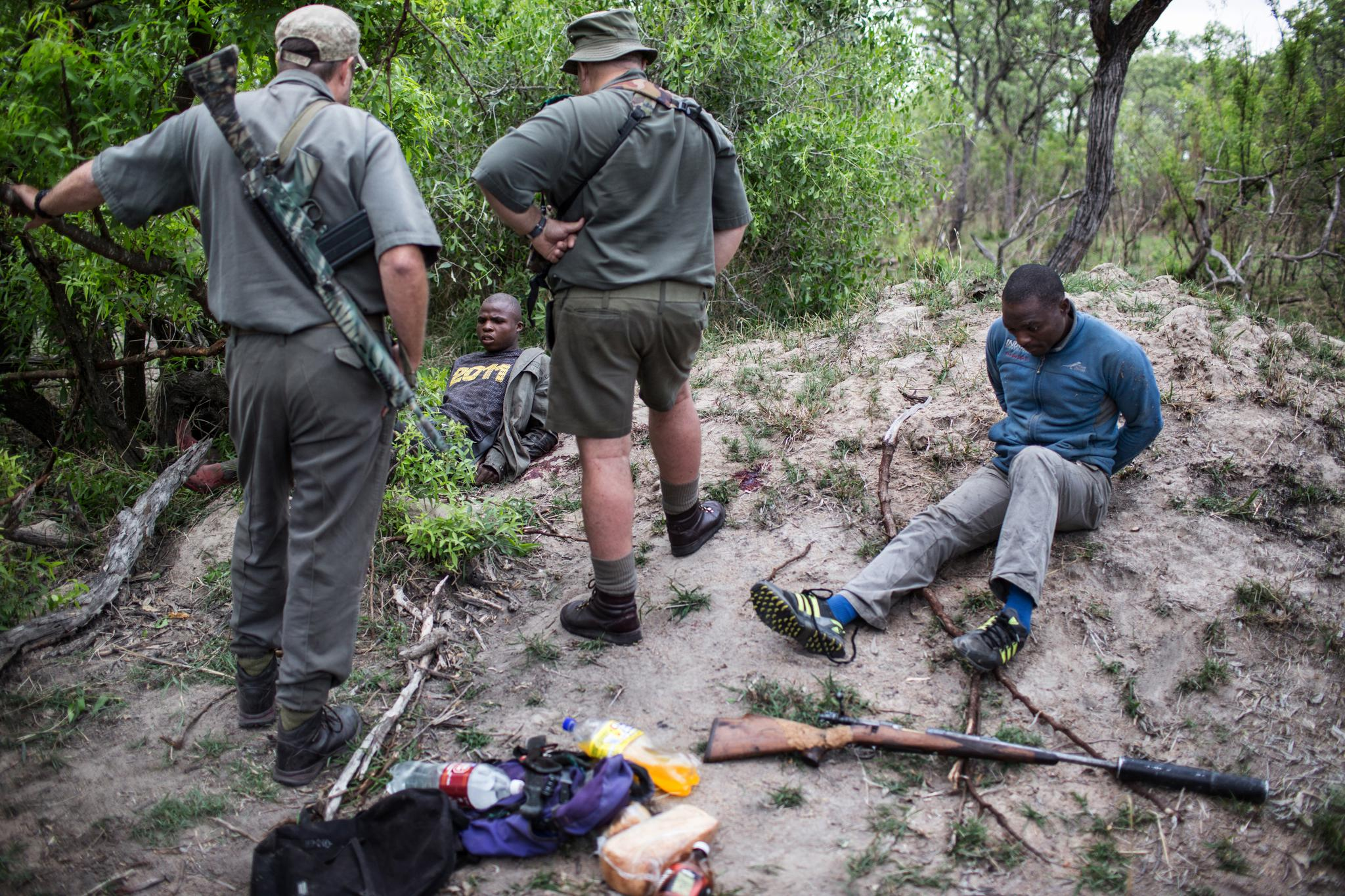 Rangers Rob Thompson and Don English with suspected rhino poachers at Kruger National Park in South Africa, on November 7, 2014.