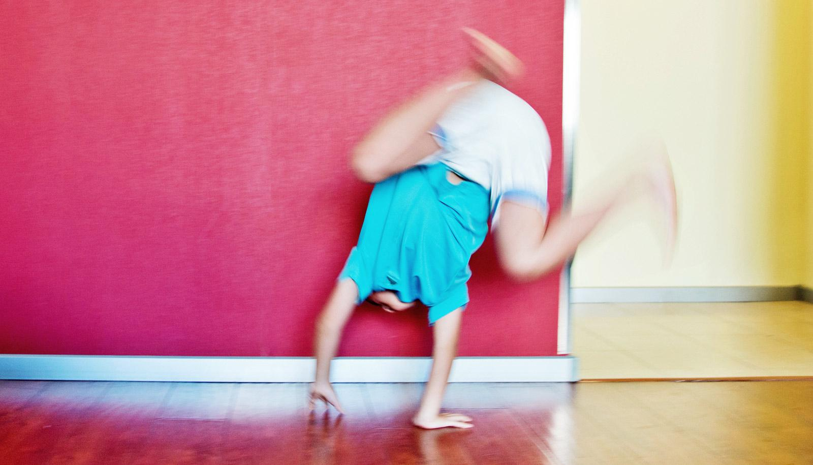 boy does handstand against red wall