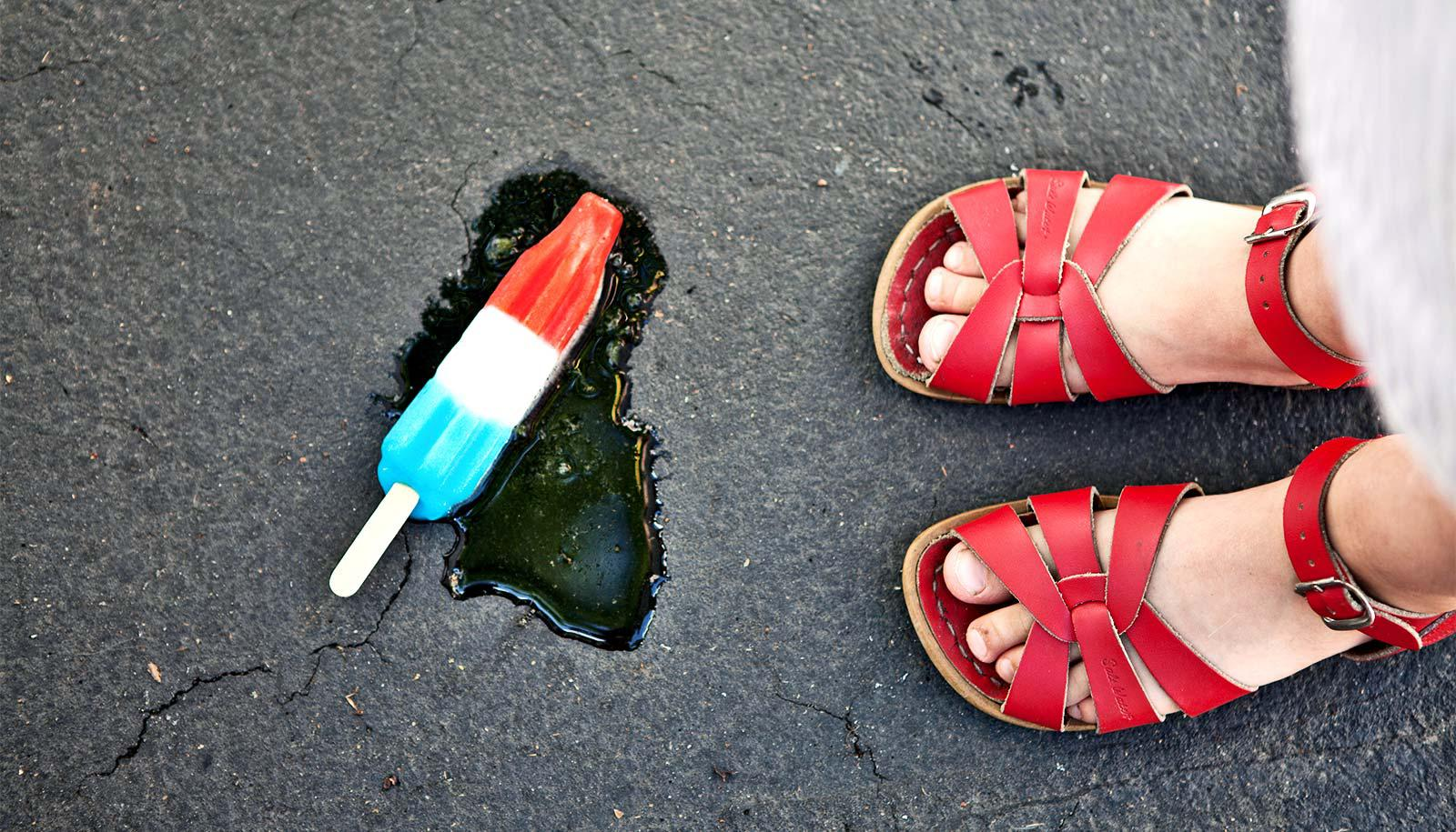 A young girl has dropped a red, white, and blue popsicle on concrete. The popsicle melts near her red sandals