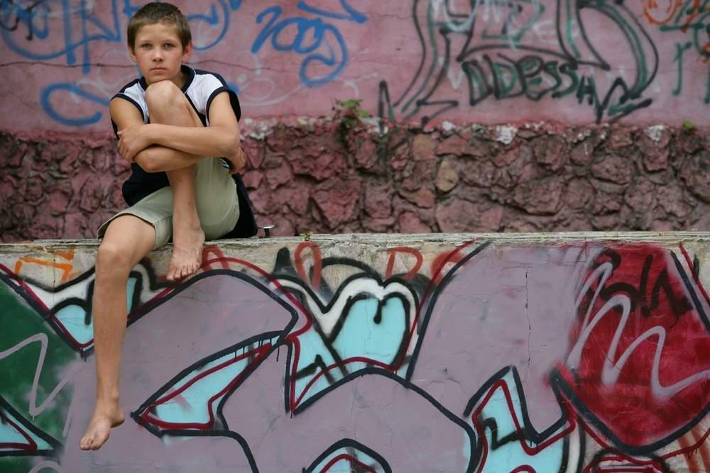 a boy sits on a graffiti covered wall