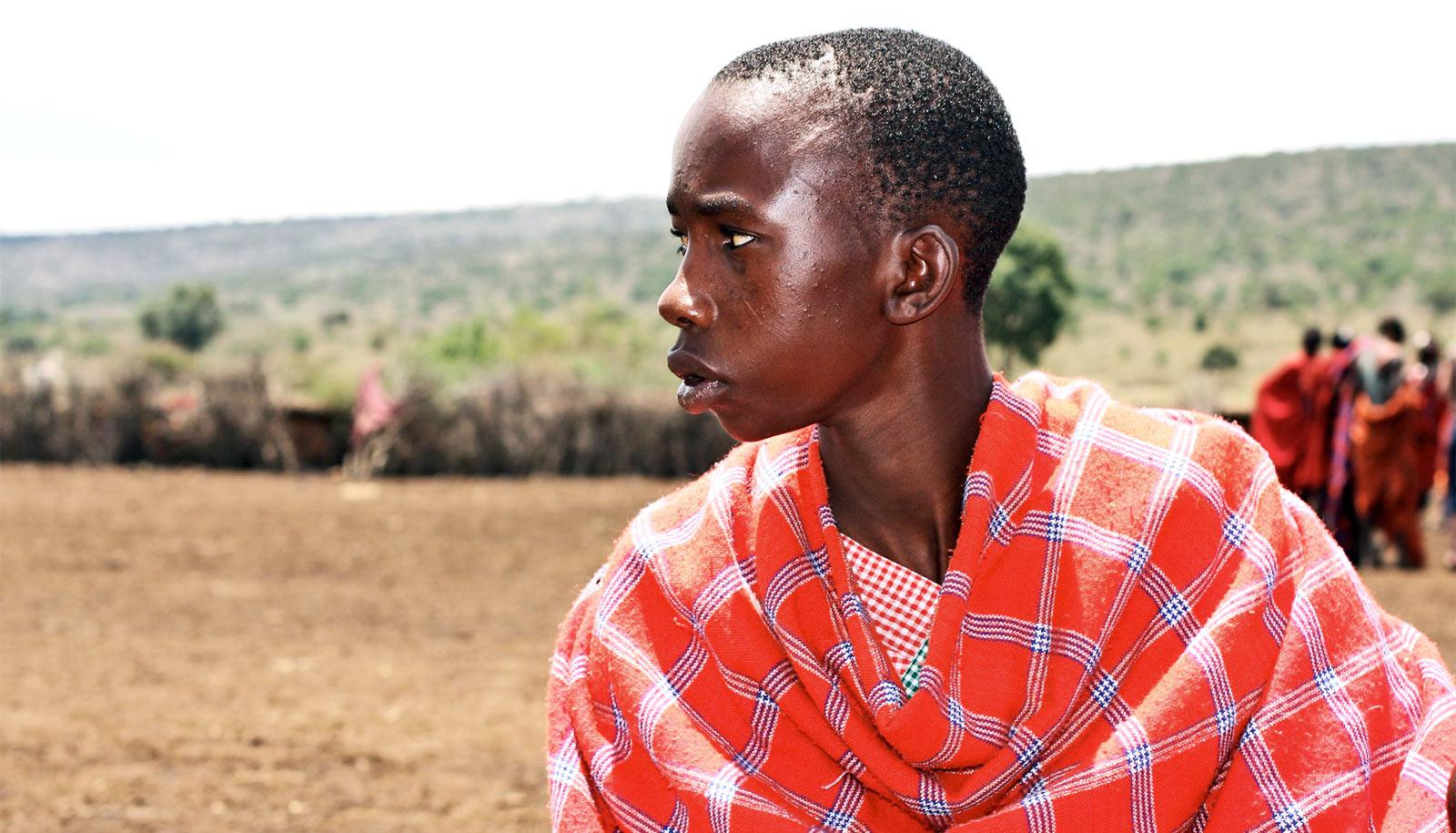 A young man from the Masai people in Kenye wears a bright orange wrap