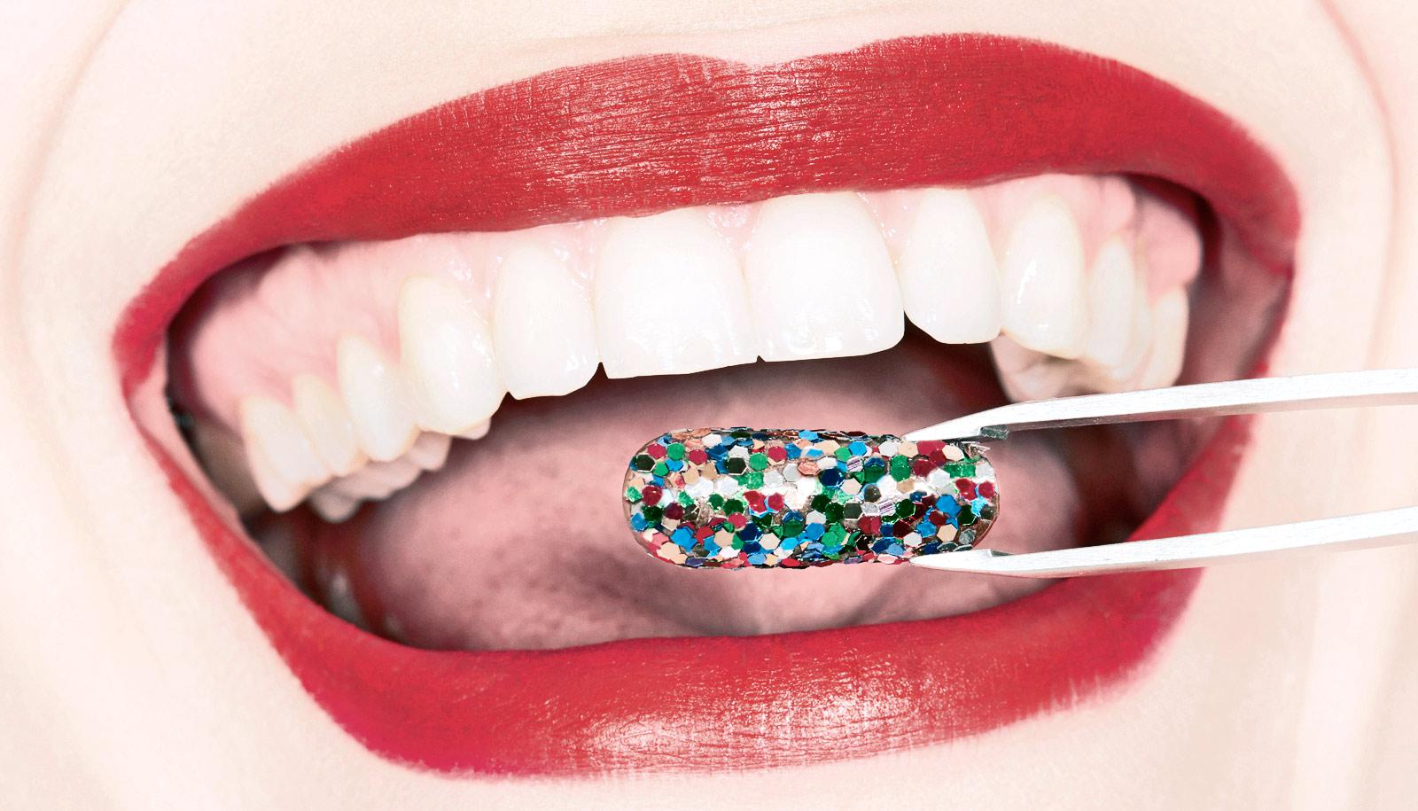 tweezers hold pill in front of mouth with red lipstick