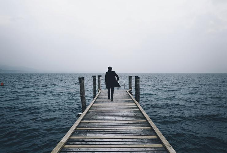 Finding Hope and Meaning at Life's End: One Doctor's Experience by Christopher Kerr. Photograph of a man walking towards the end of a dock by Alessio Lin