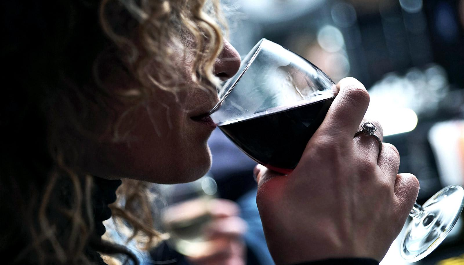 A woman with curly hair sips a glass of red wine