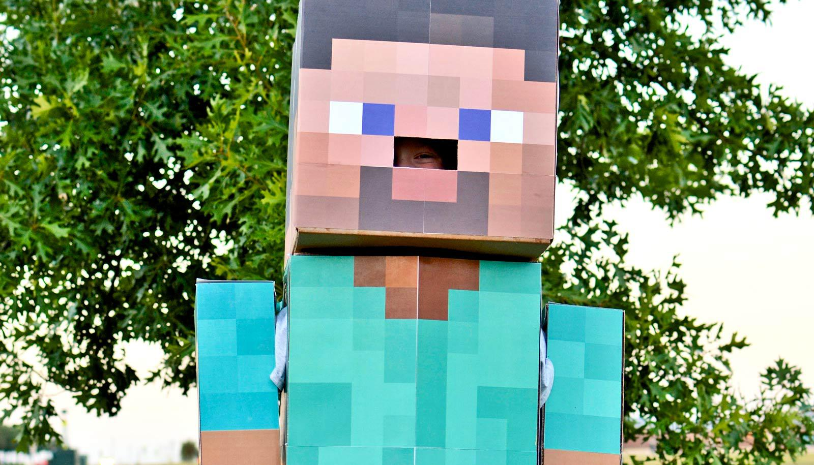 person peeks out of cardboard Minecraft costume