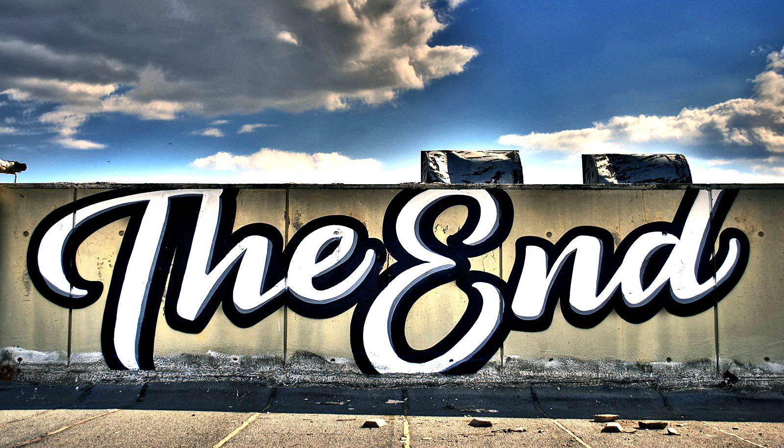 """The image shows a wall with """"The End"""" painted in large, cursive letters. (automated storytelling concept)"""