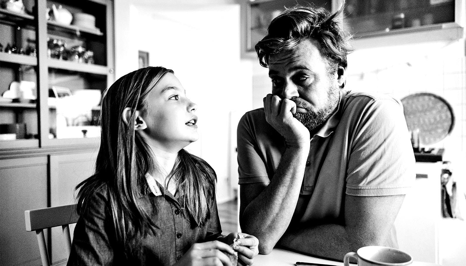 A father and daughter look at each other while sitting at the kitchen table. She looks hesitant, while he rests his face on his hand