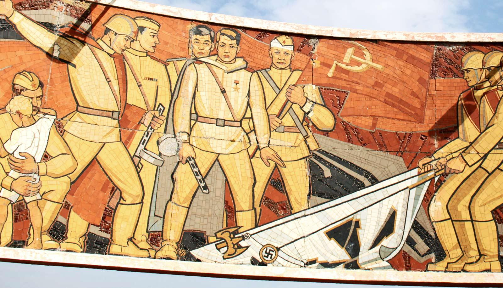 Russian war memorial shows Soviet soldiers in tan uniforms taking down Nazi flags and holding up the Soviet banner.