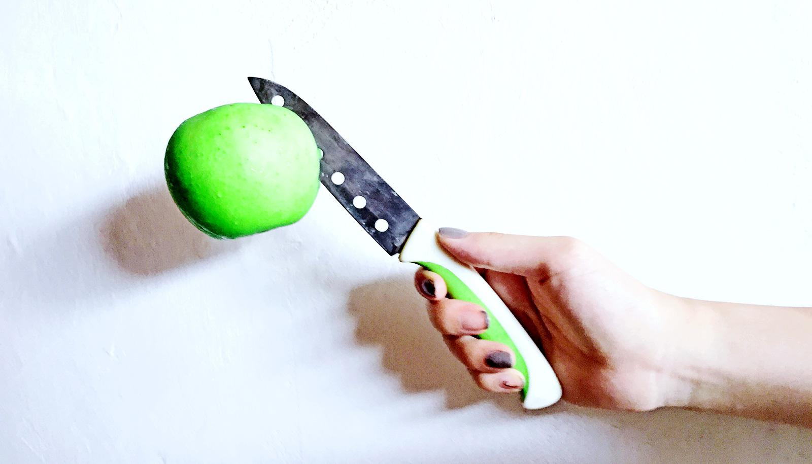 knife in apple in hand (food choices concept)