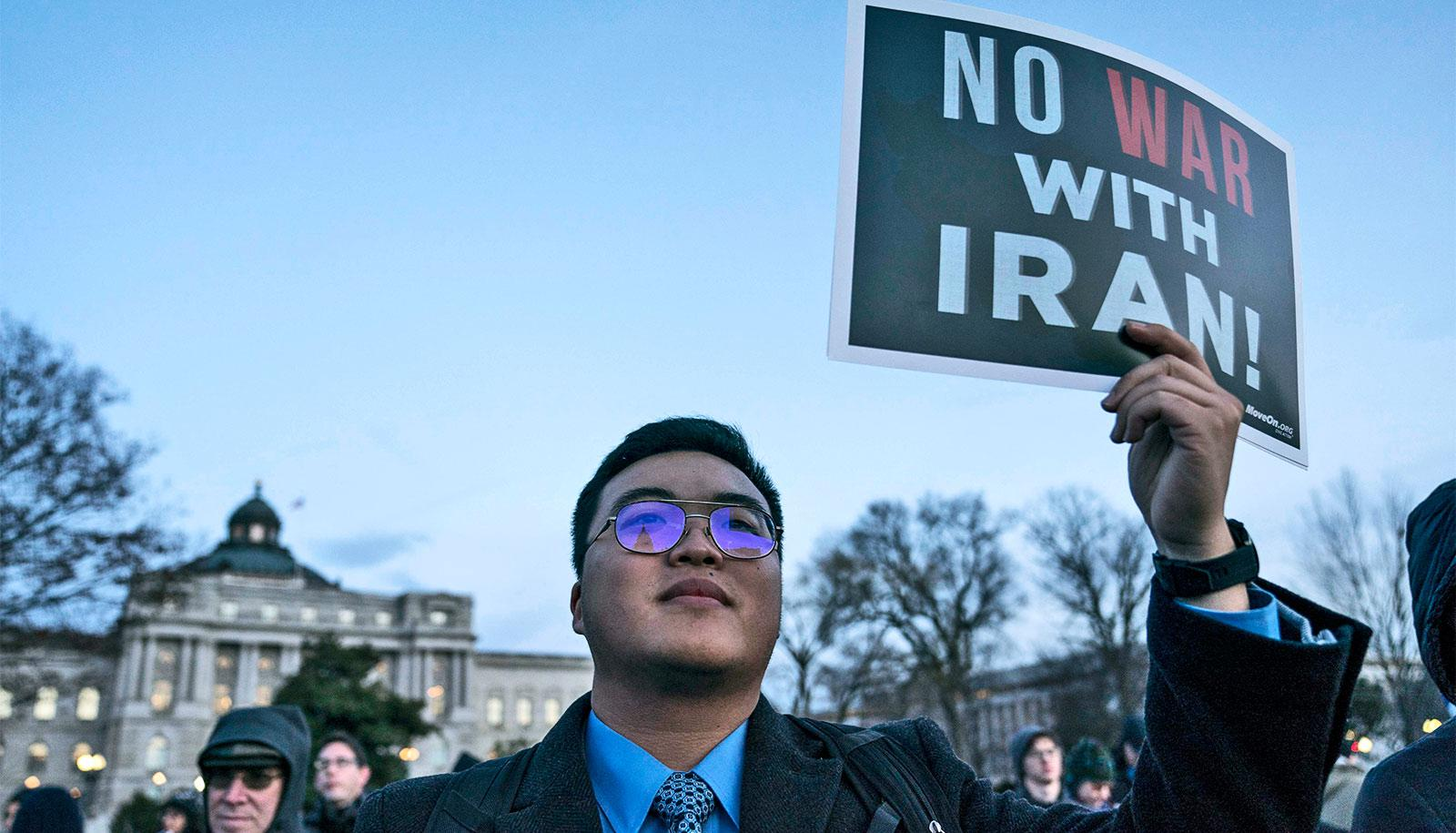 """A protestor in a suit and glasses holds a black and white sign that reads """"No War with Iran"""" with """"war"""" in red"""