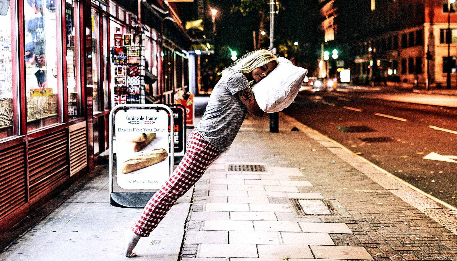 A woman leans on a floating pillow on a sitting street, almost levitating