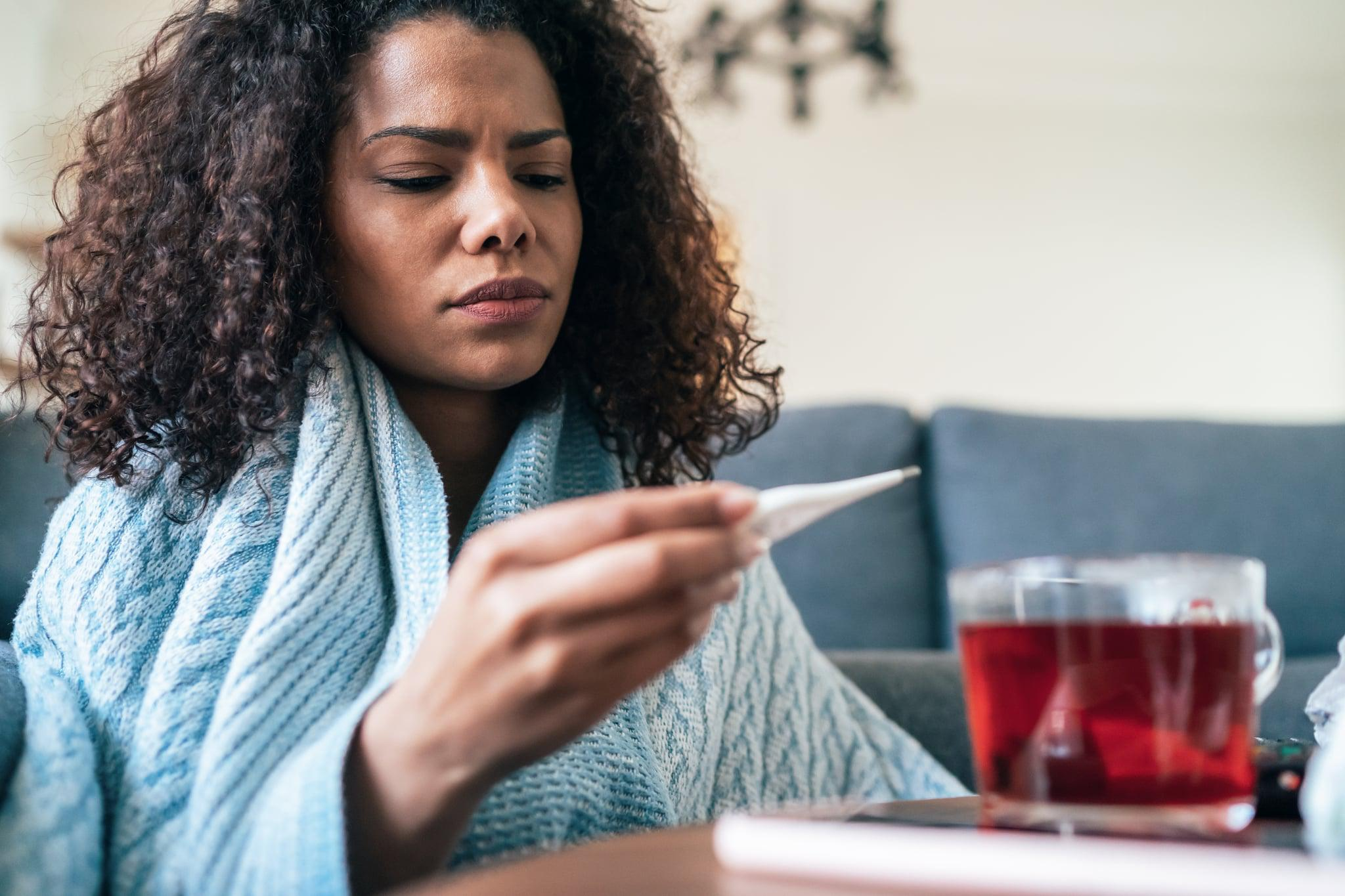 Young woman is looking at the thermometer sitting covered with blanked on the sofa at home