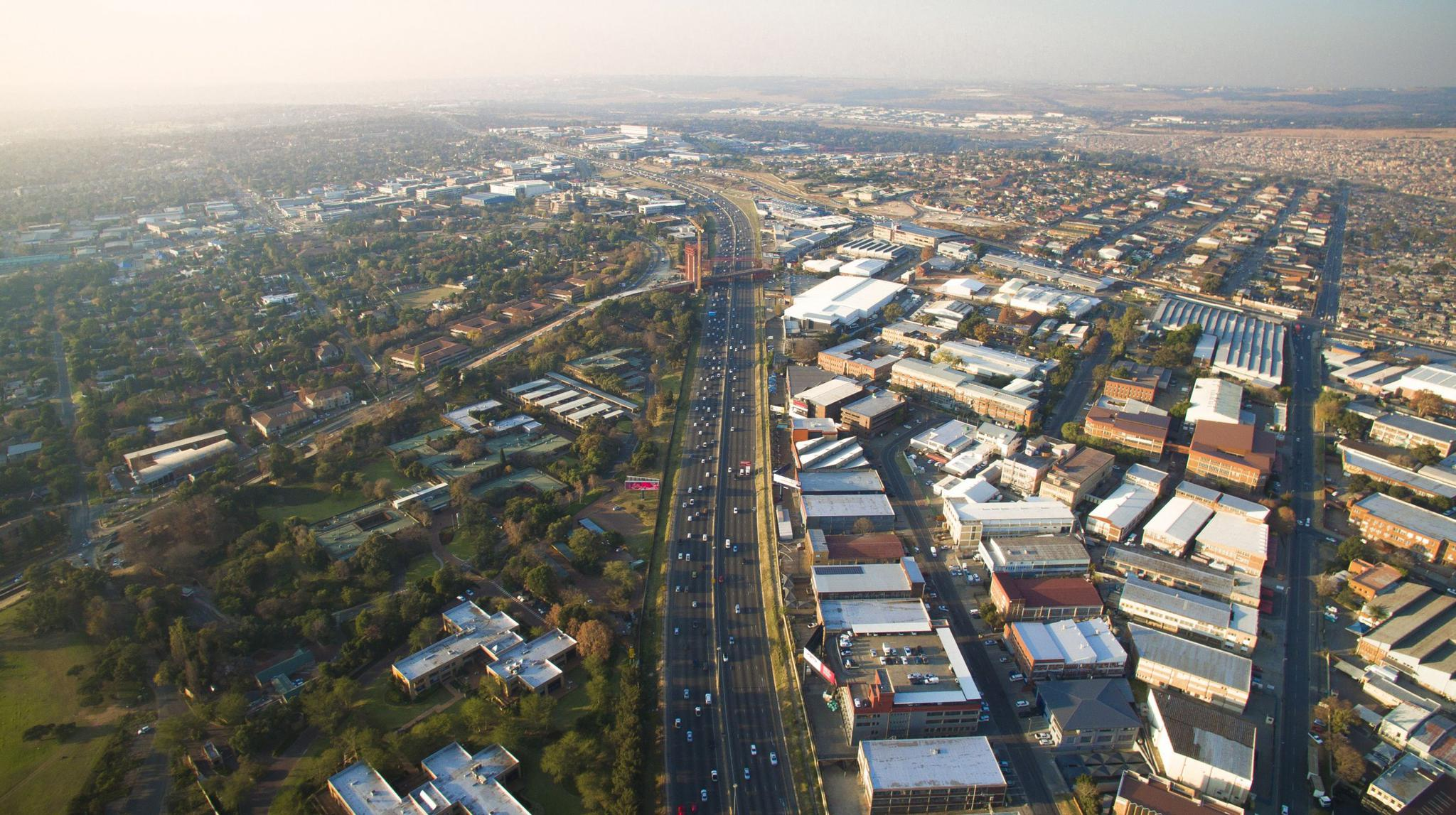 The bridge in the photograph is one of two being built that will carry bus rapid transit and pedestrians from Alexandra to Sandton. Thousands of commuters make this trip each day, on thoroughfares not designed to carry heavy pedestrian traffic. Bridges such as these, in theory, will ease access and improve the safety of commuters to Sandton.