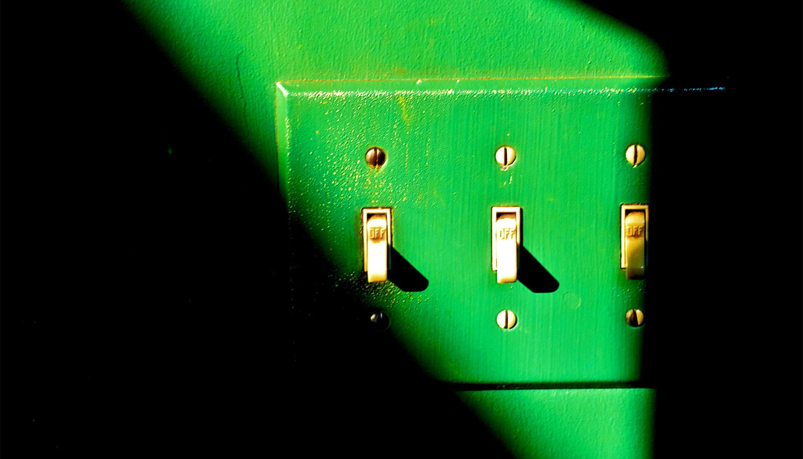 A green wall and light switch in a sliver of light in a dark room