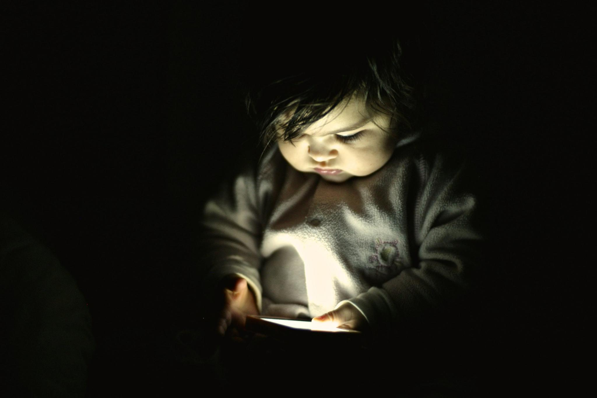 A 10-month-old baby girl looks at a smartphone screen in a dark room. Researchers found a correlation between toddlers who had half an hour per day of smartphone exposure with those who began talking later.