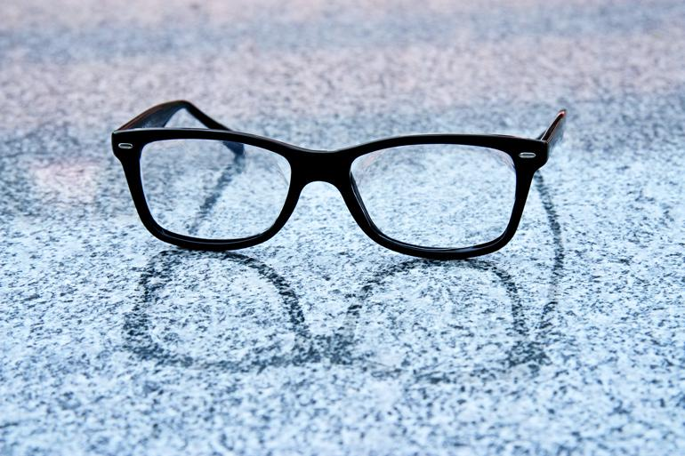 Black glasses sit on a marble-like reflective surface