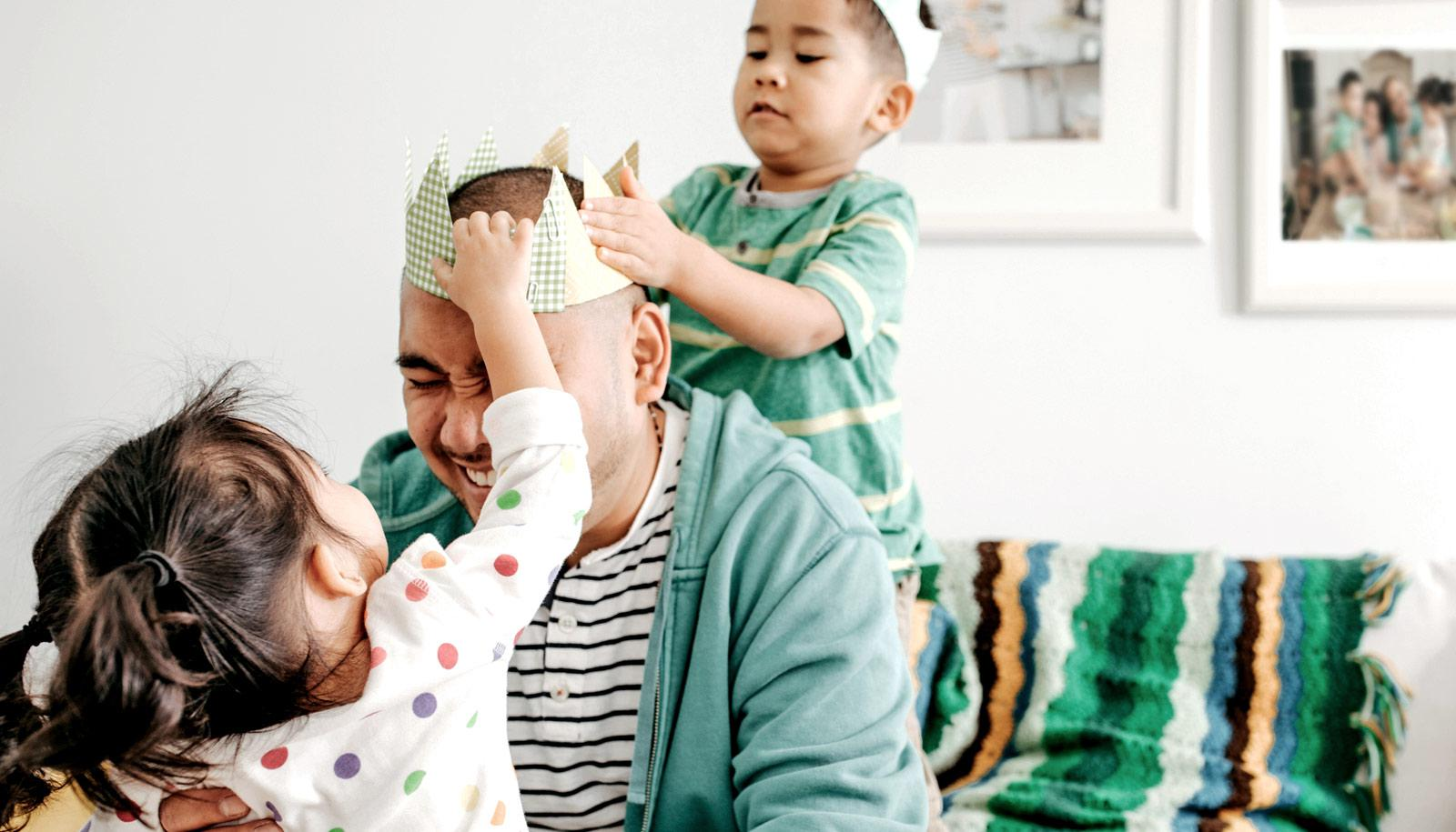 father's day - two toddlers put crown on dad's head