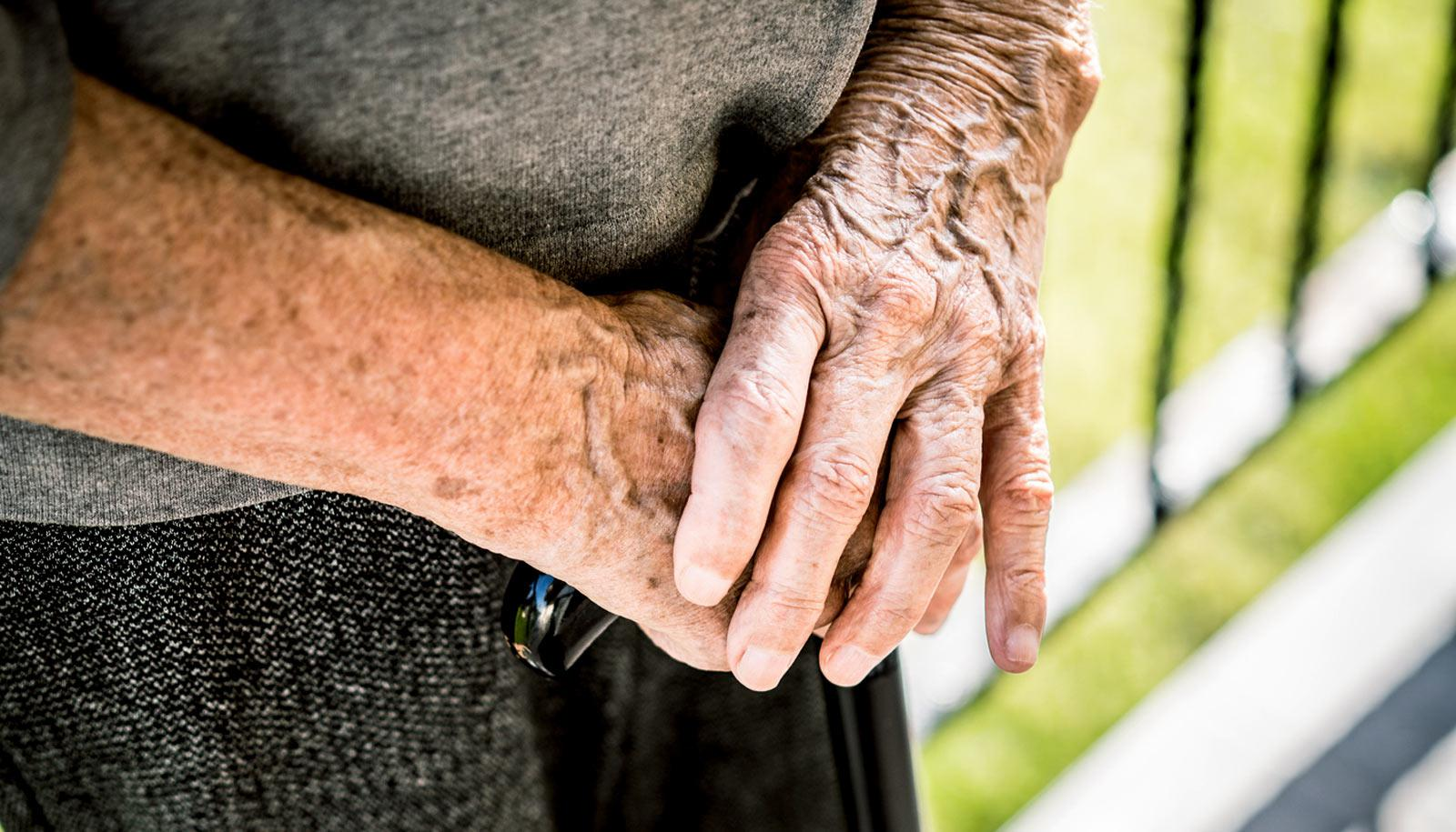 hands of elderly person holding cane