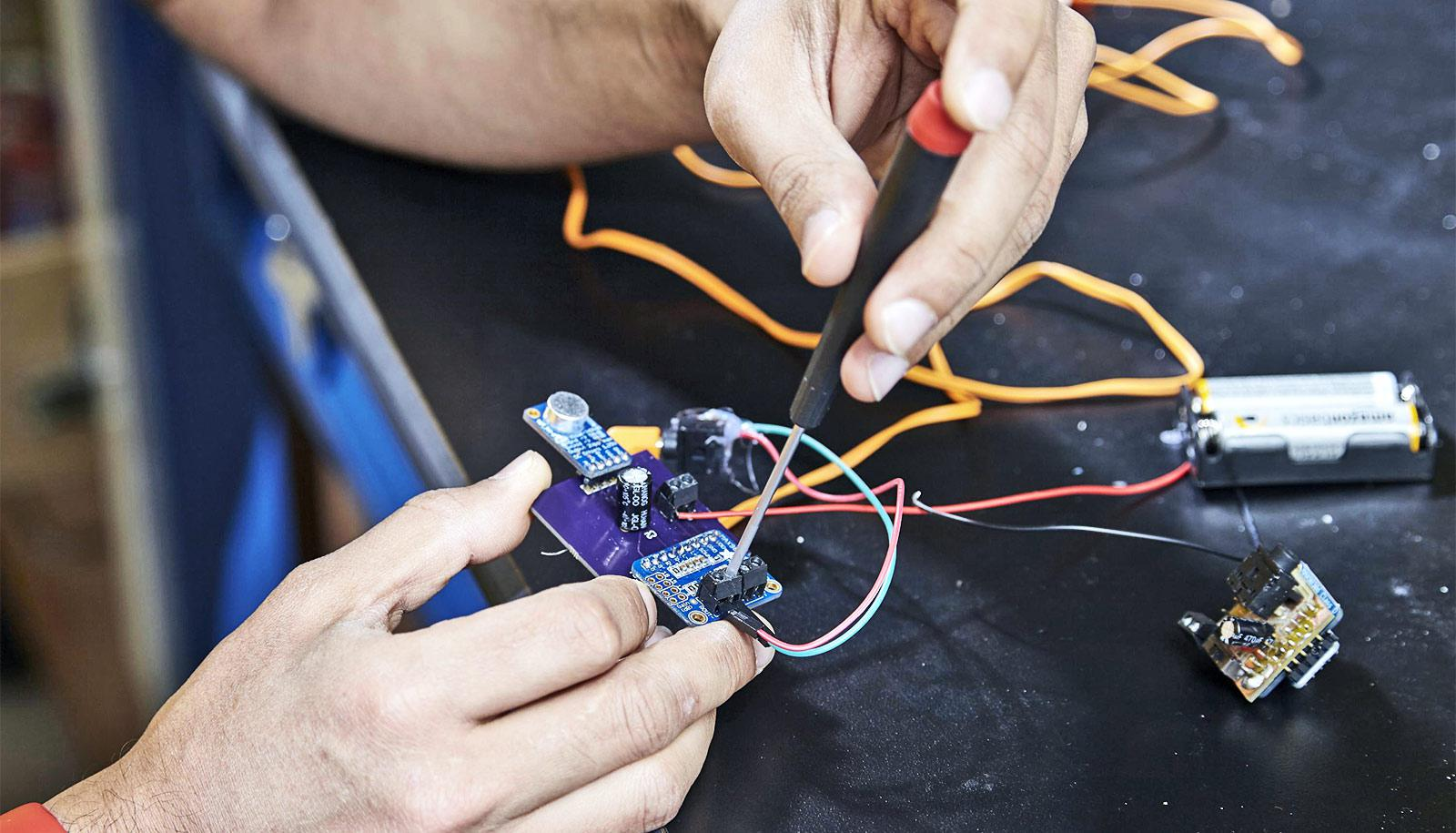A researcher works on the electronics for the hearing aids