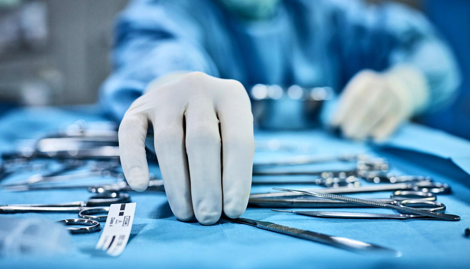surgeon picks up tool from tray
