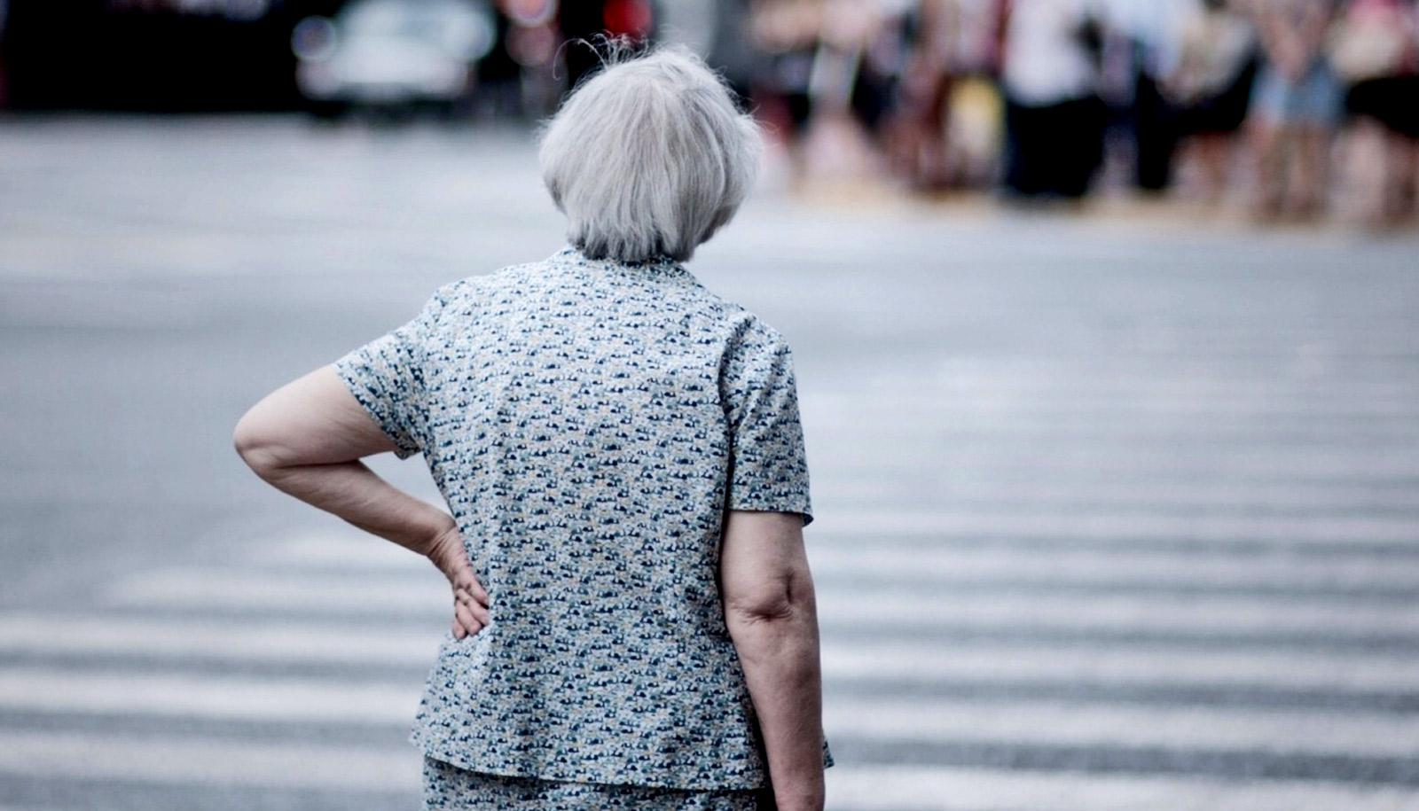elderly woman with hand on hip at crosswalk