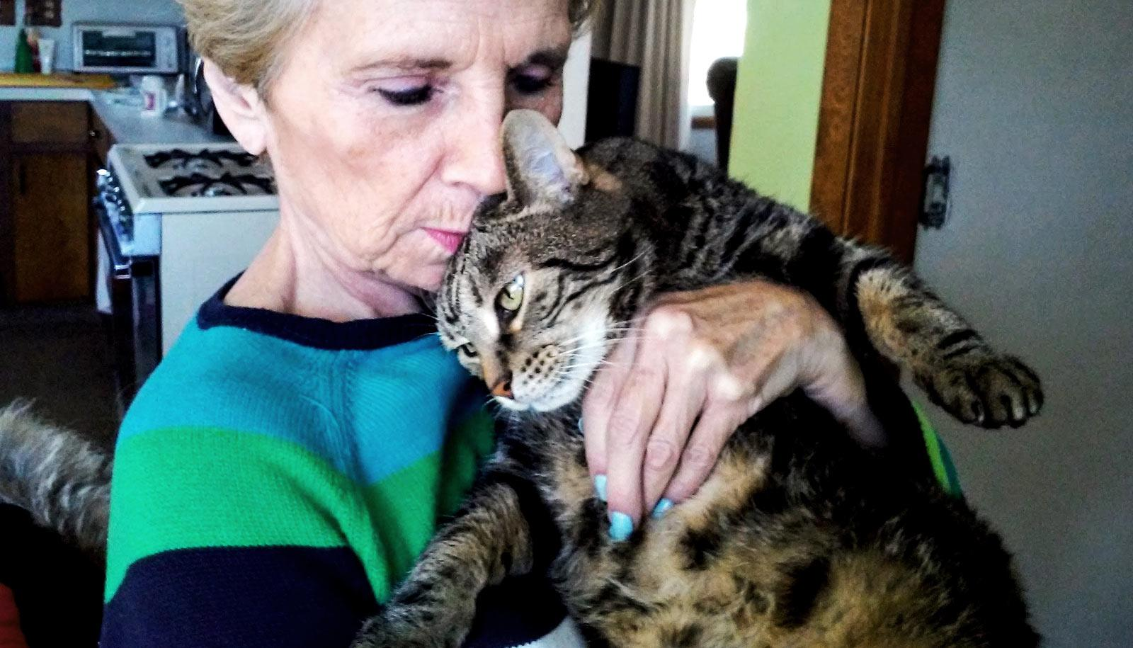 older woman holds cat