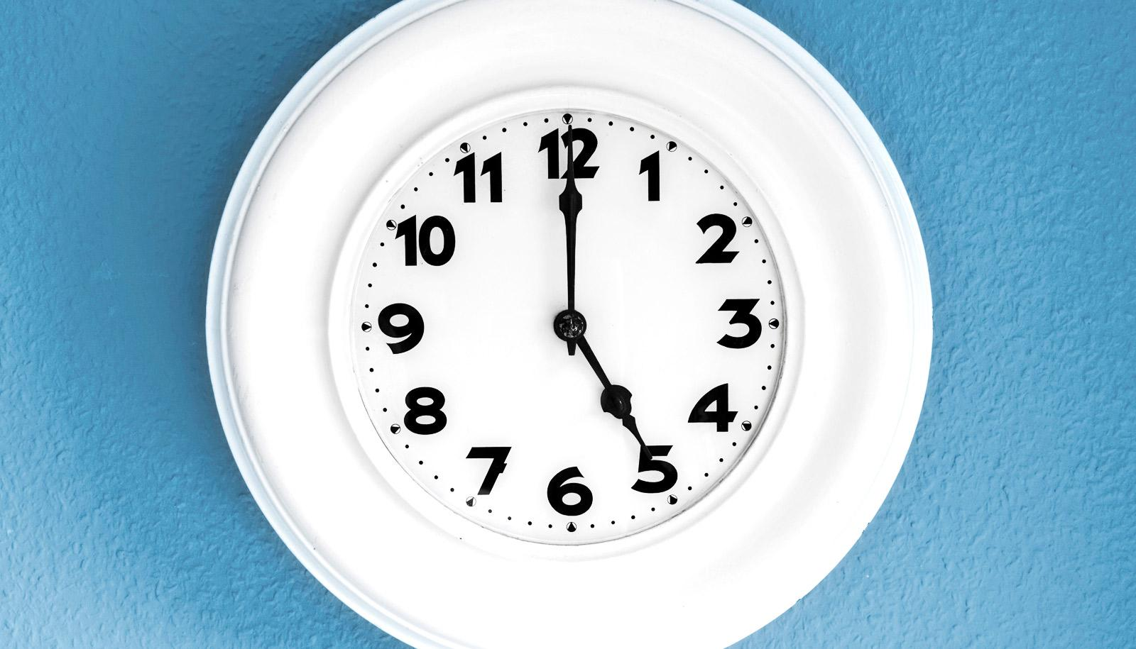 white clock says 5 o/clock on blue wall