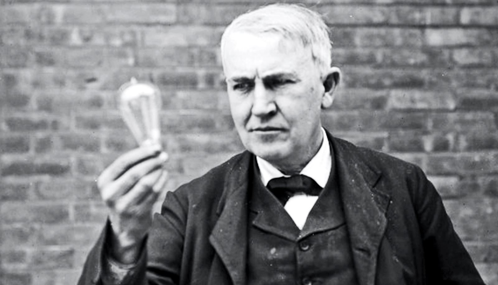Thomas Edison holds a light bulb as he stands against a brick wall