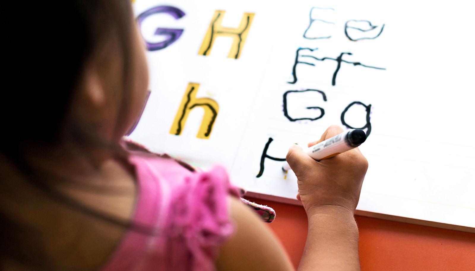 A preschool girl is writing letters in a workbook