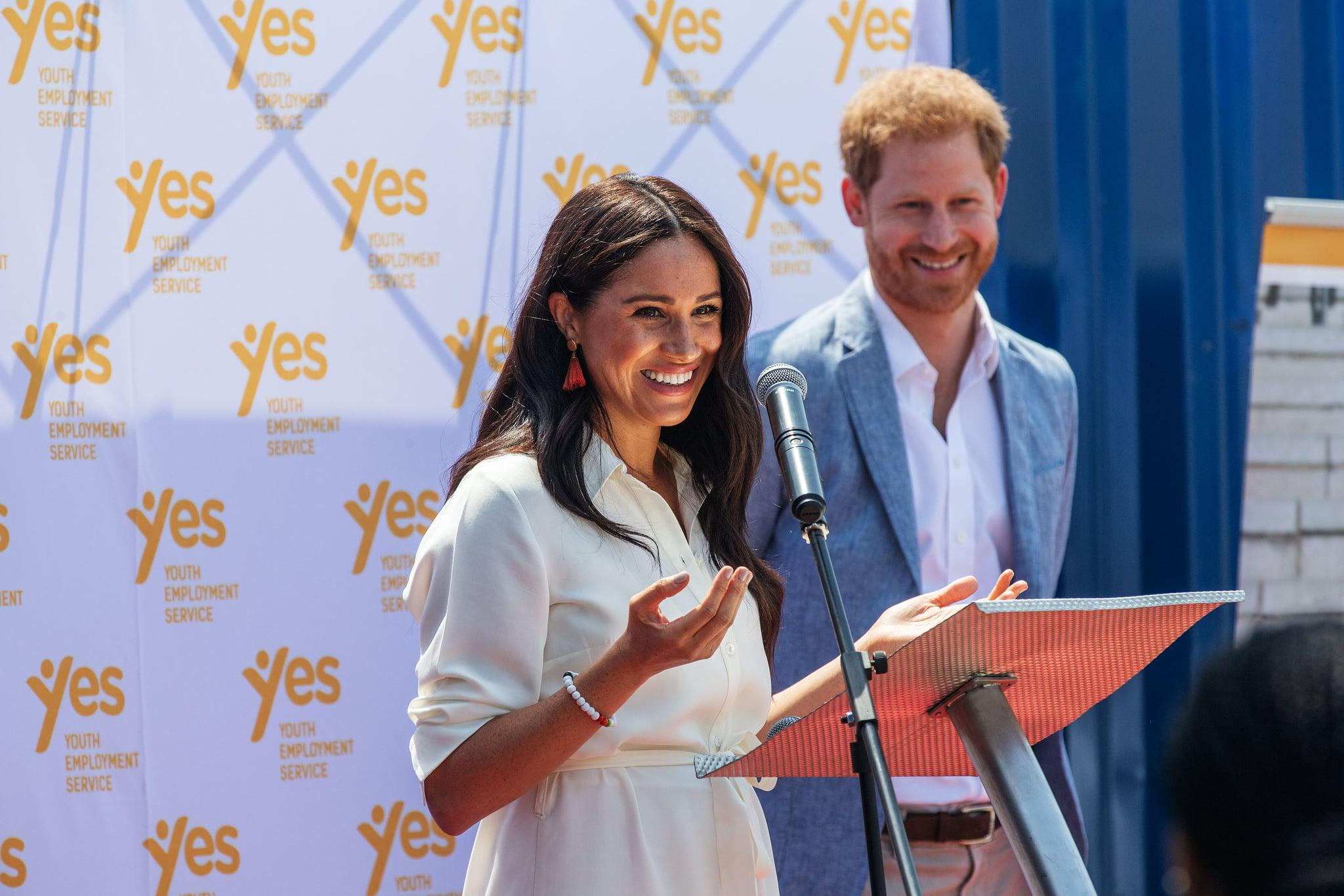 Meghan, Duchess of Sussex(L), is watched by Britain's Prince Harry, Duke of Sussex(R) as  she delivers a speech at the Youth Employment Services Hub in Tembisa township, Johannesburg, on October 2, 2019. - Meghan Markle is suing Britain's Mail On Sunday newspaper over the publication of a private letter, her husband Prince Harry has said, warning they had been forced to take action against