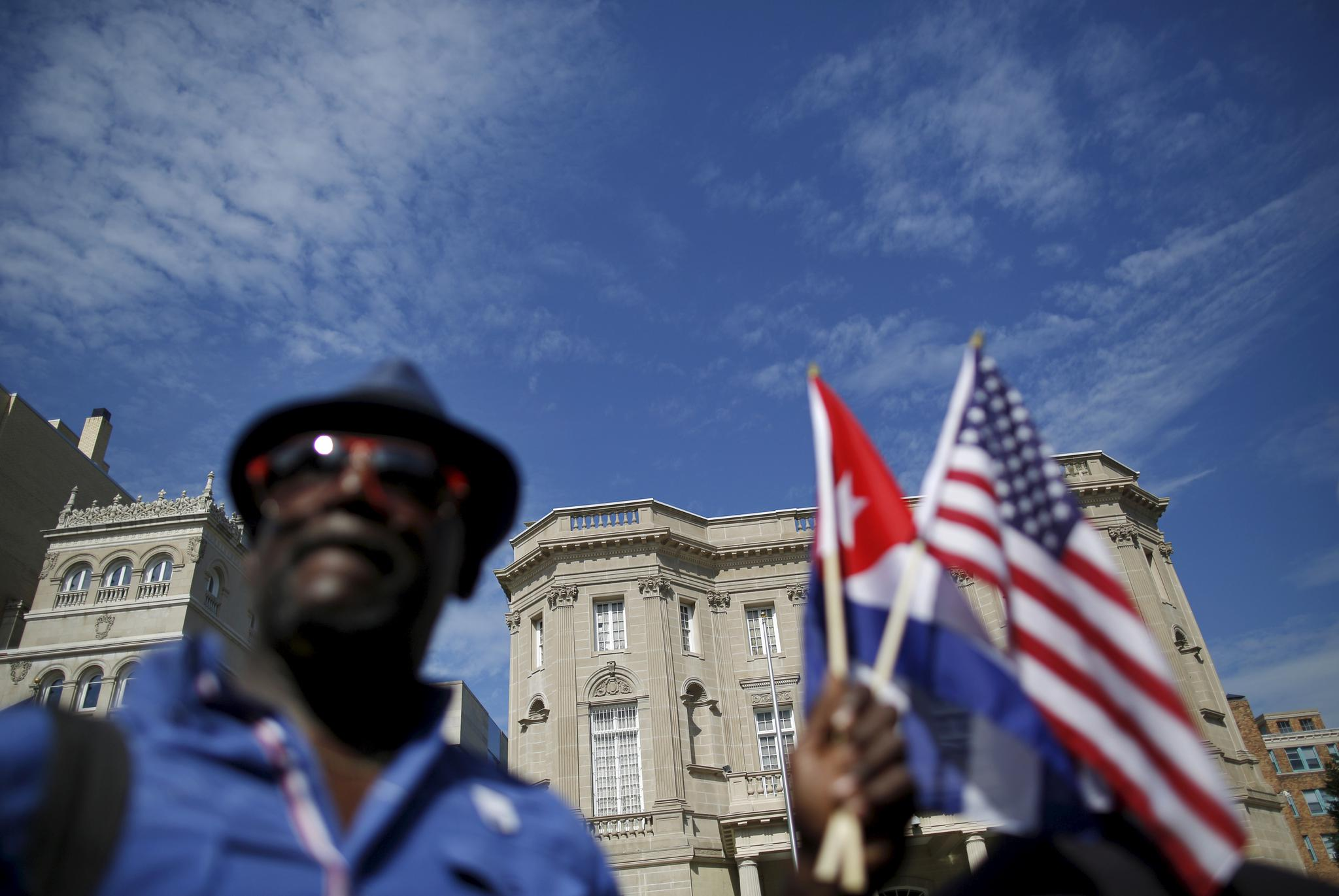 The newly reopened Cuban Embassy is seen in the background as a man holds U.S. and Cuban national flags on July 20, 2015.