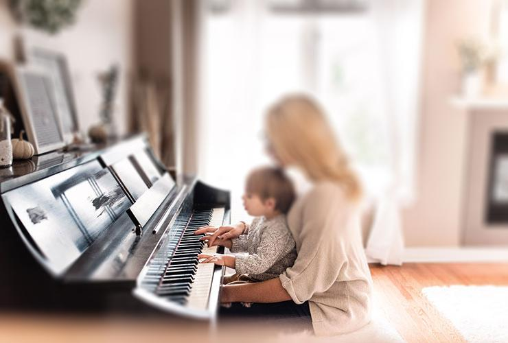 Dispelling 3 Myths of Motherhood that Sap Your Joy, Your Work & Your Children by Lauren Marie. Photograph of a mother with her child playing piano by Paige Cody