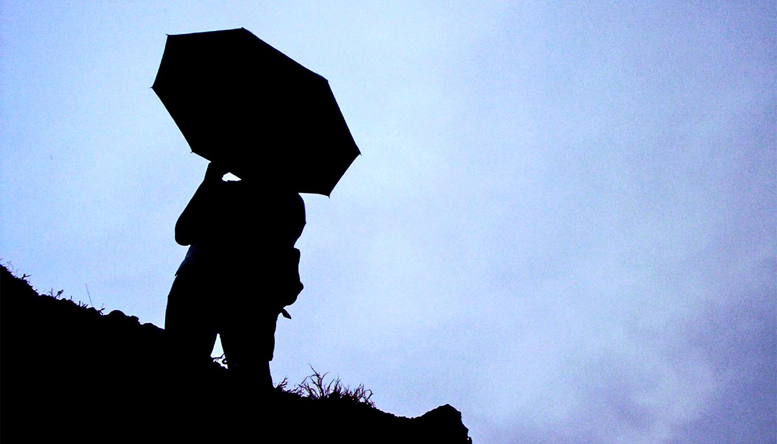 person with umbrella silhouette (Asian summer monsoon concept)