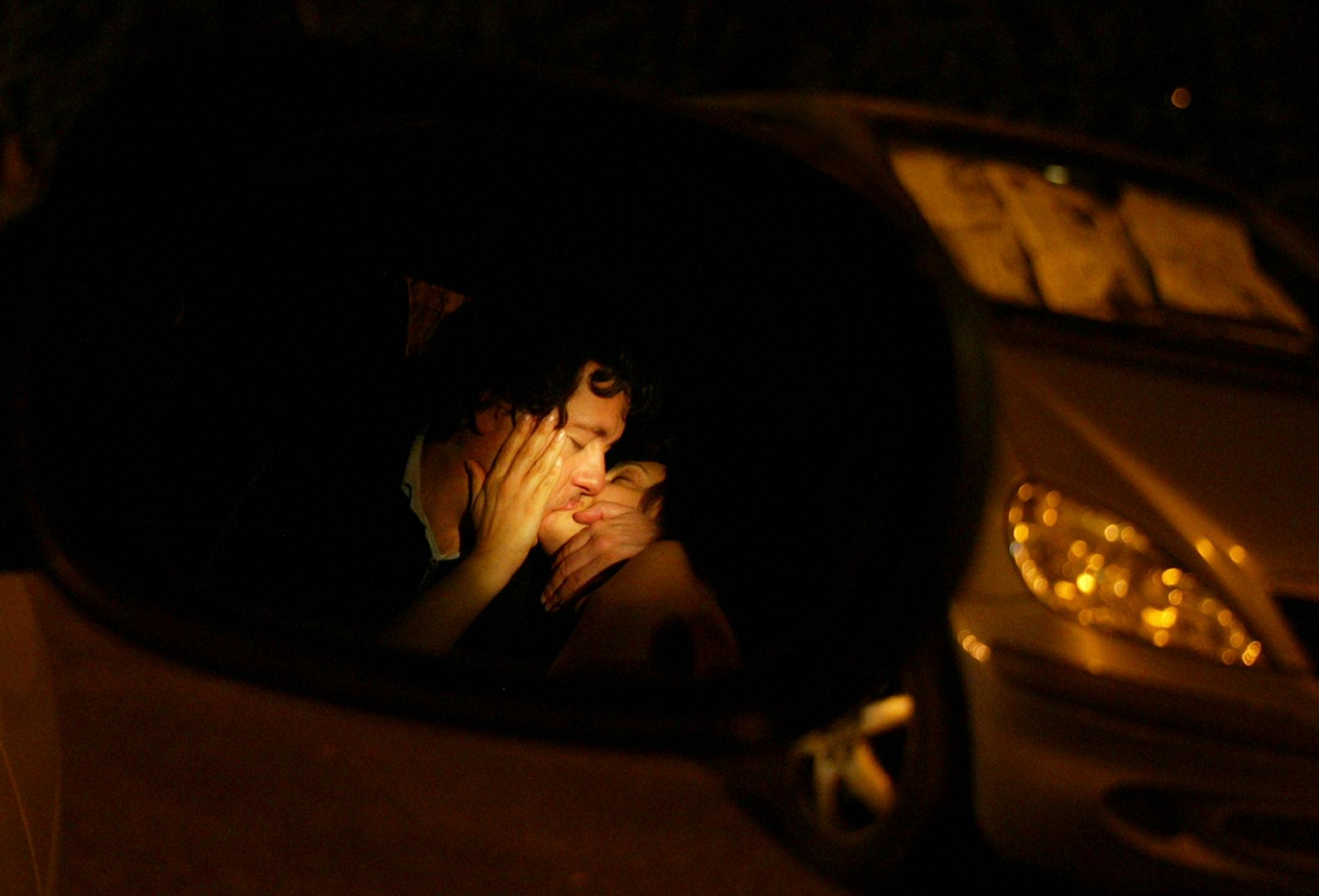 A couple kiss inside a parked car in Central Italy on early May 30, 2004.