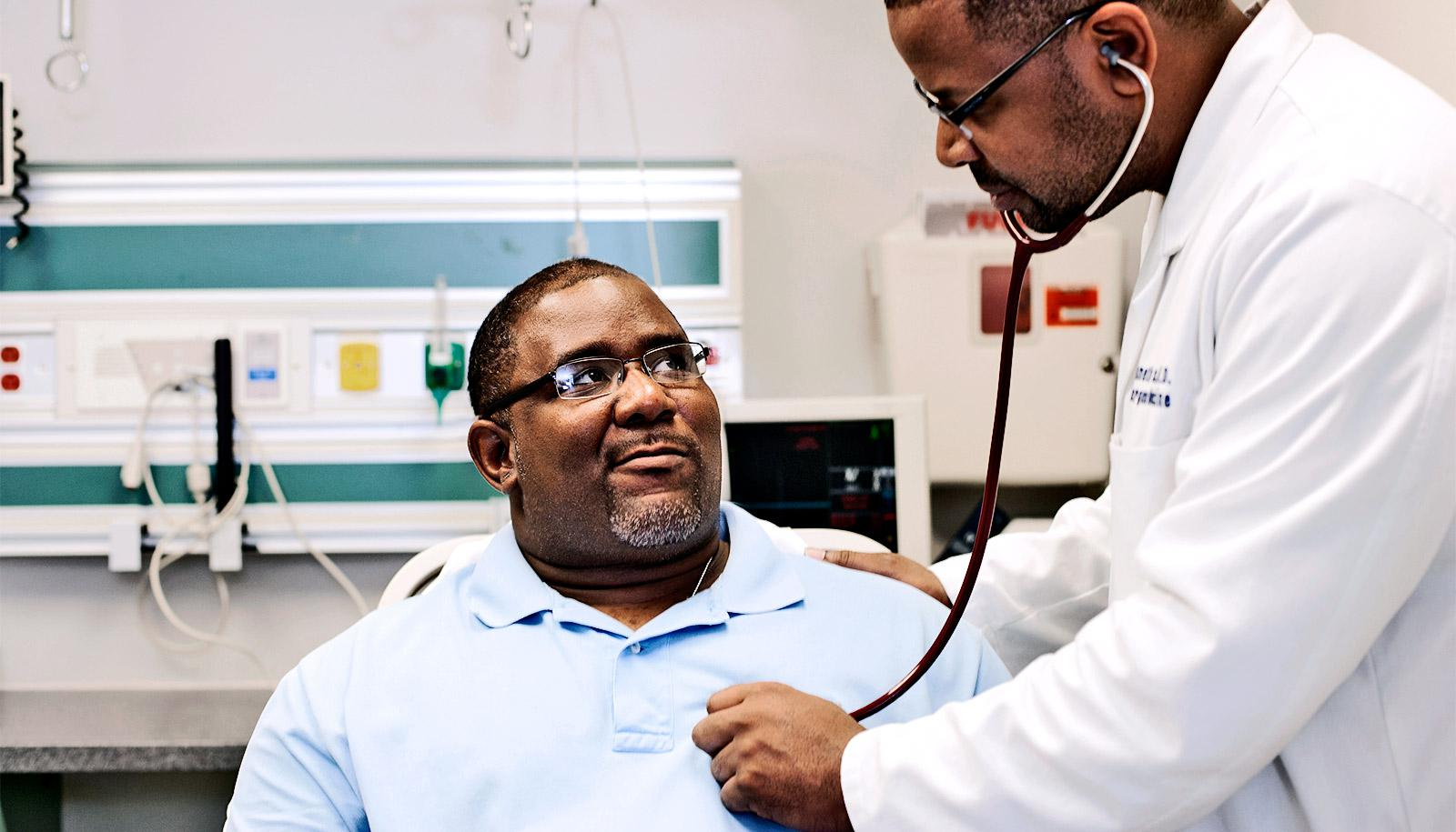 A doctor checks a man's heartbeat with a stethoscope