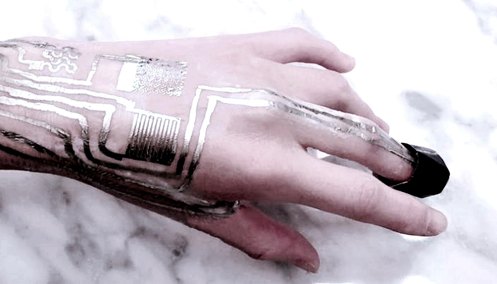 A hand has silver-looking electronics printed on it