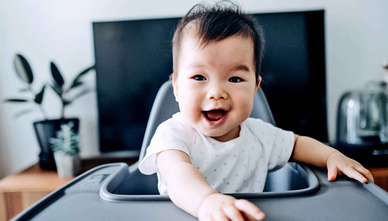 smiling baby in high chair