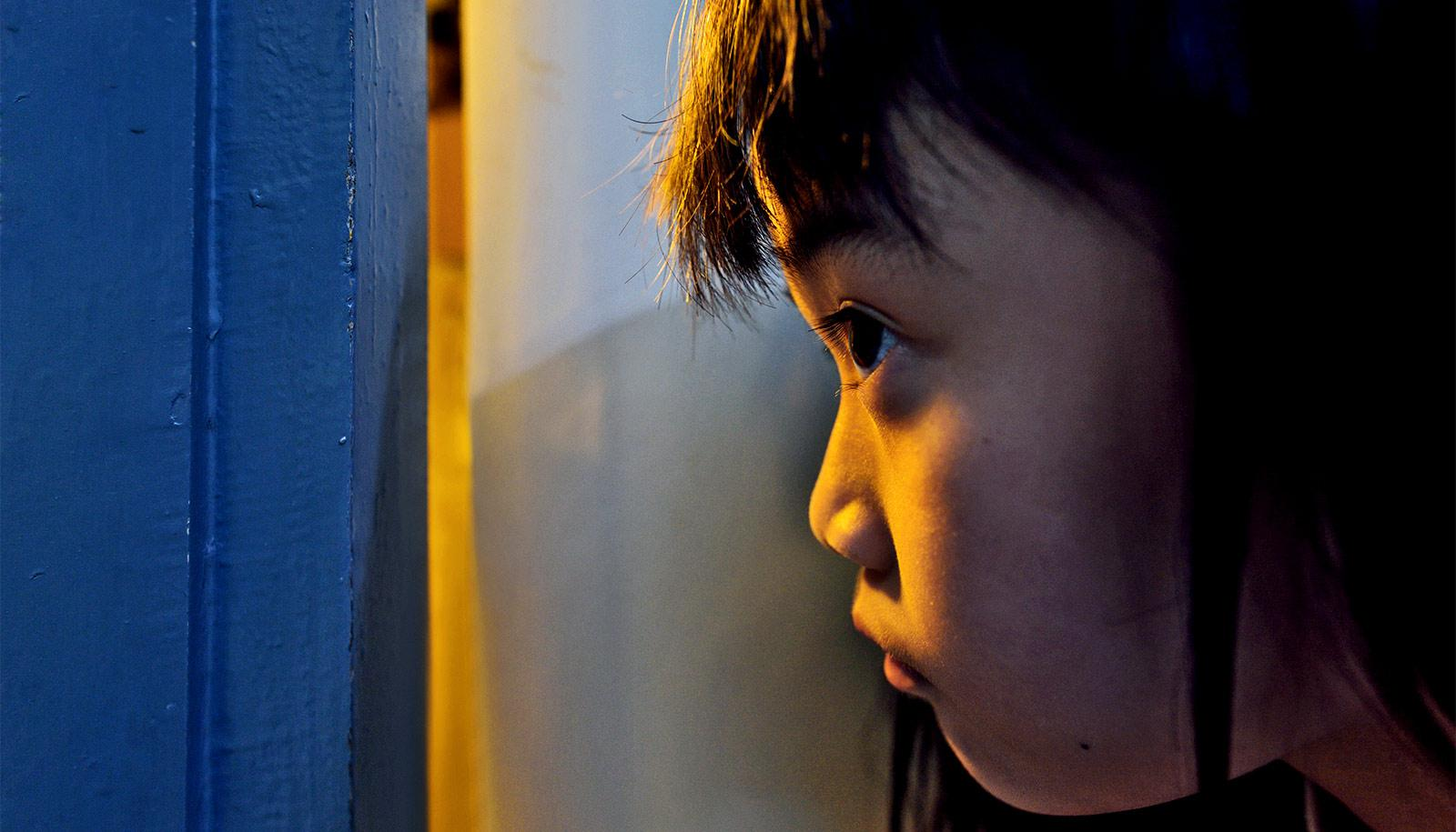 A young girl looks through a slightly-opened door